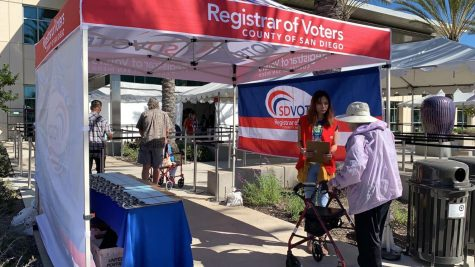 A woman in a purple jacket approaches a registrar of Voters tent in San Diego CA