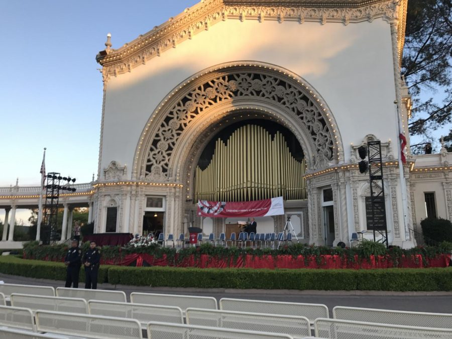 The Organ Pavilion at Balboa Park, the top part is illuminated by light, there are two police officials at the distance.