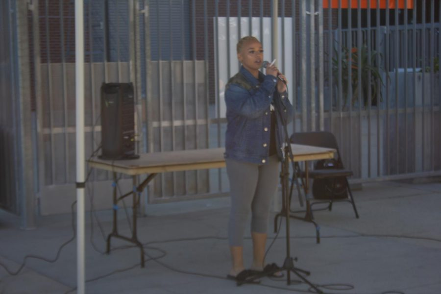 Women wearing a blue jacket, performing at City College.
