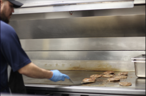 Man in a blue shirt wearing gloves and flipping burgers.