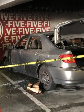 Silver can burned down with windows shattered in the SDCC parking lot.