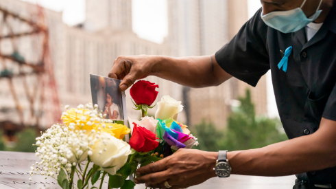 Mourner places a photo with flowers at the 9/11 Memorial & Museum