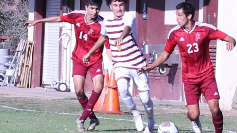 (From right) Roberto Perez advancing the ball downfield against Victor Valley College Aaron Felix with teammate Javier Monarrez trailing.